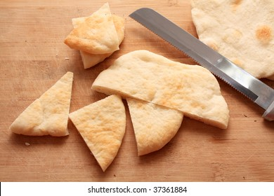 sliced pieces of pita bread on a wood cutting board