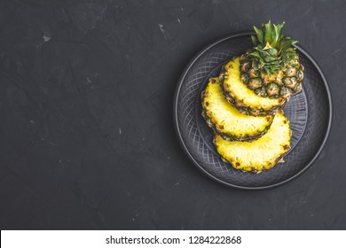 Sliced pineapple in ceramic plate on black stone concrete textured surface background. Top view with copy space for your text.