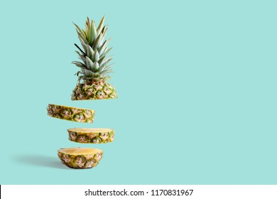 Sliced pineapple on pastel blue background. Minimal fruit concept.