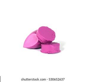 Sliced pink lipstick sample on white background