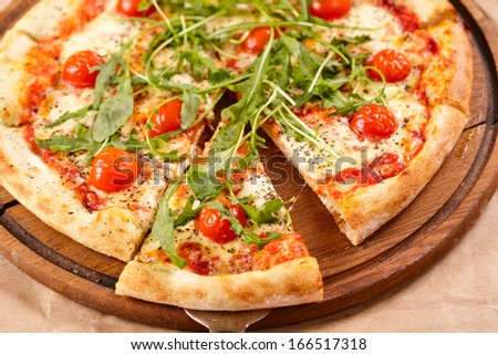 Sliced pizza with arugula and cherry tomatoes on wooden board
