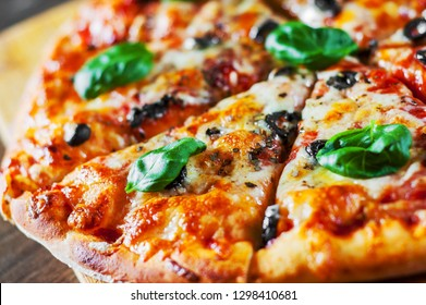 sliced Pizza with Mozzarella cheese, Tomatoes, pepper, olive, Spices and Fresh Basil. Italian pizza. Pizza Margherita or Margarita on wooden table background