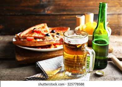 Sliced pizza served with beer on wooden table