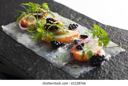 Sliced poached lobster served with assorted dressing, placed on textured black platter.