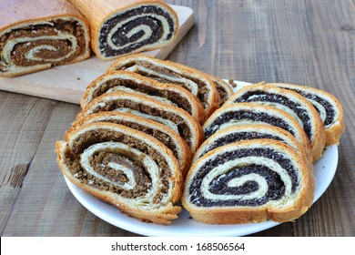 Sliced poppy seed and walnut rolls on wooden table. Loaves of holiday pastry with ground poppy seed and ground walnut filling called beigli.