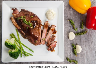 Sliced pork steck with pepper sauce served on white dish top view on wood texture background