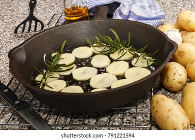 sliced potato with rosemary and oil in a cast iron pan