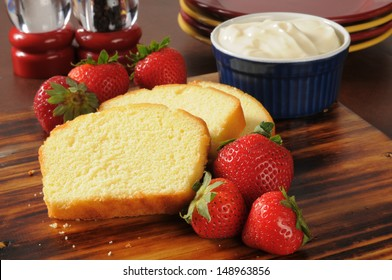 Sliced pound cake, fresh strawberries and whipped cream on a cutting board