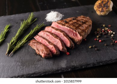 Sliced prime ribeye steak on black stone plate. Medium degree of steak doneness. With rosemary and peppers. Fork and knife.