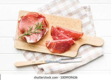 Sliced prosciutto crudo on cutting board.