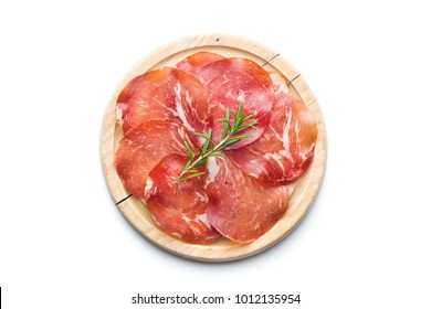 Sliced prosciutto crudo on cutting board isolated on white background.