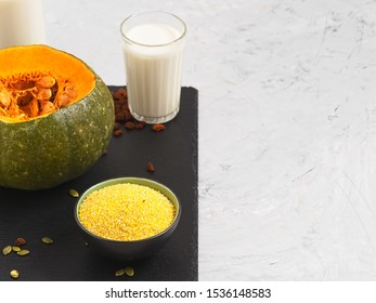 Sliced pumpkin for cooking porridge in the oven. In the foreground is a bowl of corn grits next to a glass of milk. Close-up. Copy space.