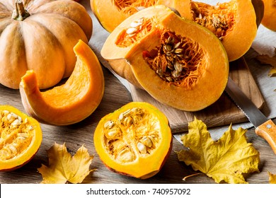 Sliced pumpkin with seeds on a wooden background. Close-up