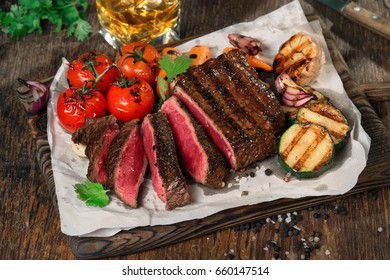 Sliced rare grilled steak on rustic cutting board with set of grilled vegetables on dark wooden rustic table with glass of whiskey close up