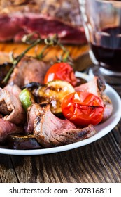 Sliced rare roast sirloin of beef with roasted vegetables on rustic wooden background