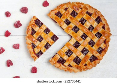 Sliced raspberry pie with fresh sugared raspberries on white table
