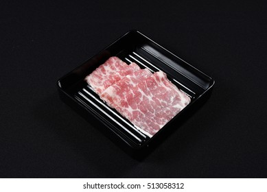 Sliced raw beef shank on a black plate