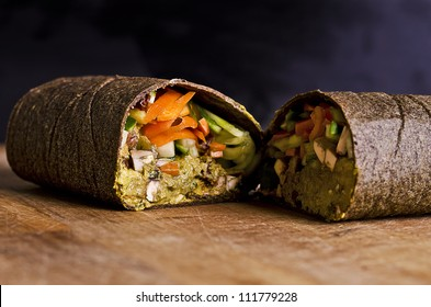sliced up raw food wrap with vegan ingredients and green pesto on a wooden plate