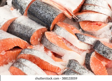 Sliced raw, not cooked salmon, red fish, lying in the ice on the counter in the supermarket. Fresh fish
