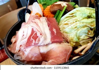 Sliced raw pork,Fresh vegetables, Carrots, Lettuce, Japanese Onion, Shiitake mushroom with sauce in black shabu,preparing for cook.food ingredients for shabu,japanese food