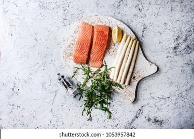 Sliced raw uncooked salmon fillet on wooden chopping board as fish shape with ingredients for cooking dinner arugula, white asparagus over white marble texture background. Top view, space.