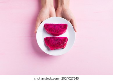 Sliced red dragon fruit or pitaya on white dish holding by hand on pink background, Tropical fruit