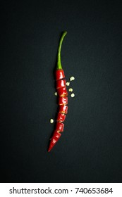 Sliced red hot chili pepper showing seeds over black background