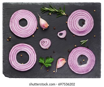 Sliced red onions set with spices and herbs on black stone background.Top view