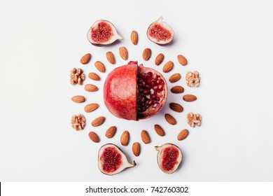Sliced red pomegranate fruit with almonds and figs, walnut on pastel white background. Minimal flat lay concept. Pastel colors.