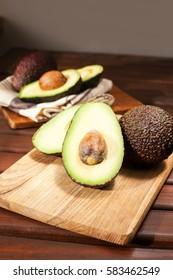 Sliced ripe avocado on wooden cutting board. Indoor vertical closeup still-life image.