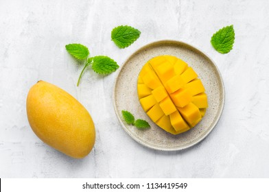 Sliced ripe mango fruit with mint leaves on concrete background. Top view.