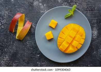 Sliced ripe mango fruit with peel on dark background. Top view.