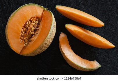 Sliced ripe melon on black background, dark style food seen from above.
