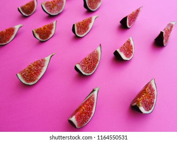 Sliced ripe sweet figs on a purple/pink background. Mediterranean fruits, healthy and sweet snack. Side whew. Overhead. Space for text.
