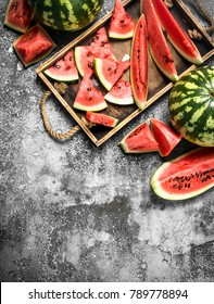 Sliced ripe watermelon on a wooden tray. On a rustic background.