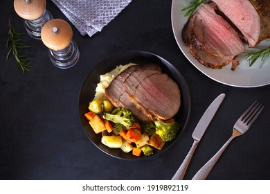 Sliced roast beef with mashed potatoes and vegetables. Overhead horizontal photo
