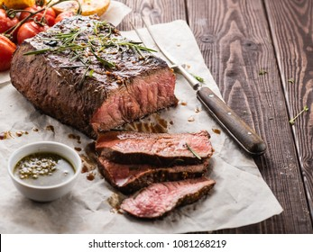 Sliced Roast beef on white paper on wooden table with grilled vegetables