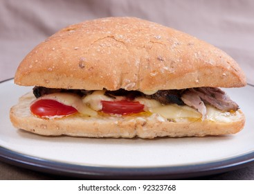 sliced roast beef sandwich on ciabatta bread with melted cheese, tomatoes and butter