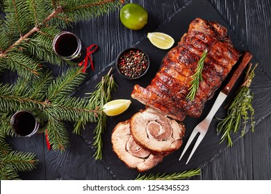 sliced roast pork roulade -  Porchetta, delicious pork roast of Italian culinary holiday tradition on a slate tray with fir-tree and red wine, close-up, flatlay