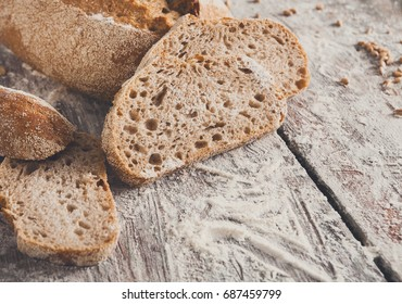 Sliced rye bread, bakery background on rustic wood, closeup, copy space