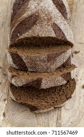 Sliced rye bread on wooden table. Top view, close up