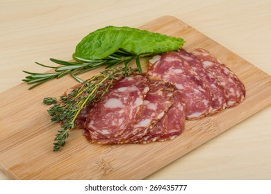 Sliced Salami with herbs on the wooden bckground