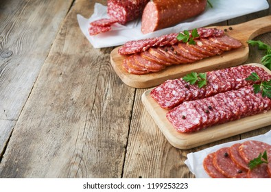 Sliced salami with parsley on a wooden cutting board
