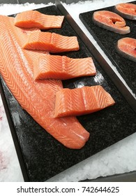 Sliced salmon stakes on black tray chilled with ice on displayed in fish market.
