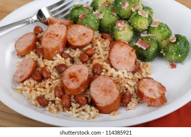 Sliced sausage and beans on rice with brussels sprouts