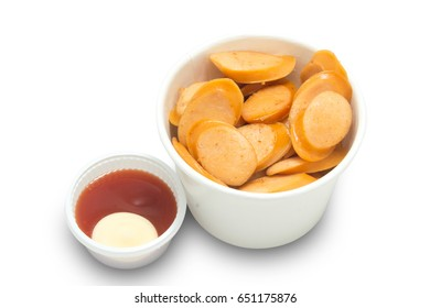 sliced sausage in a cup with sauce isolated on white background