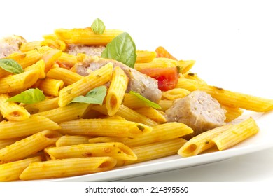 Sliced sausage with penne pasta and red tomato sauce with basil leaves
