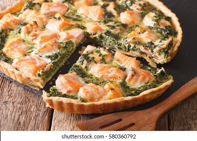 sliced Savory quiche with salmon and spinach, close-up on the table. Horizontal