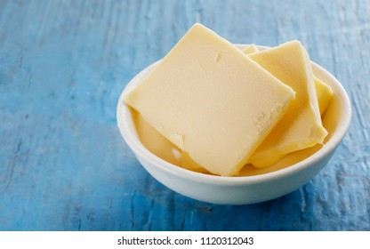 Sliced slabs of fresh butter in a small dish to be served as an individual accompaniment to a meal with bread or pastries