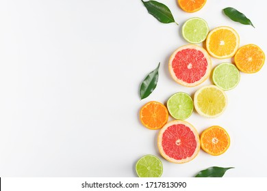 Sliced slices of citrus fruits laid out on a white table. Flat lay, top view. Fruit's background
